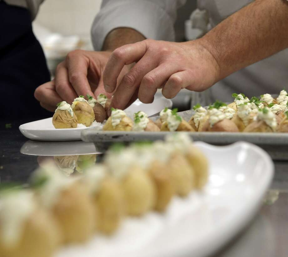 Chef Andrew Cain of Sante prepares appetizers during the Top 100 Newcomers fundraising dinner for the San Francisco/Marin Food Bank at The Cavalier in San Francisco, Calif., on Sunday, July 27, 2014. The Chronicle helped organize the dinner as part of the Eat Drink SF festival. Photo: The Chronicle