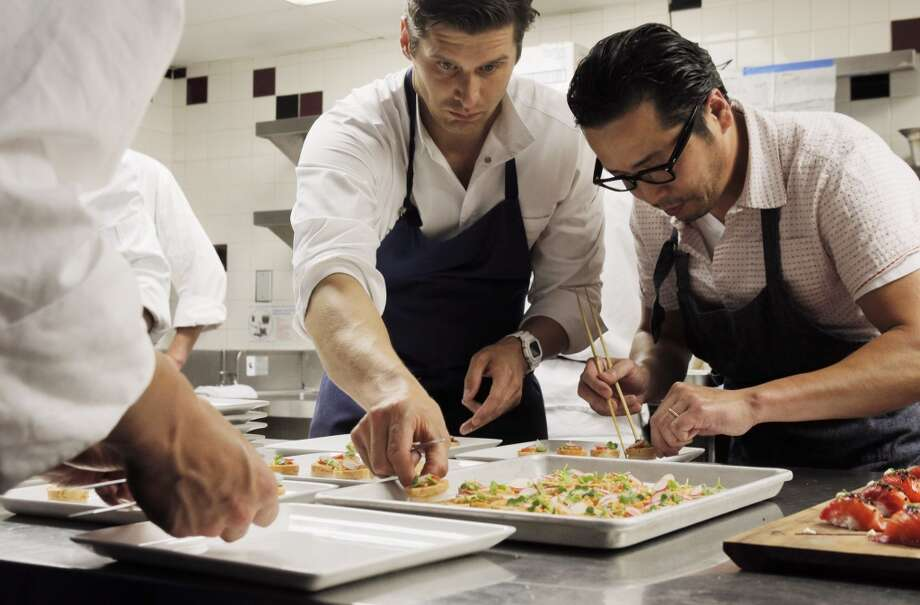 Chefs Nico Delaroque, left, and Shotaro Kamiyo, right, prepare appetizers in the kitchen during the Top 100 Newcomers fundraising dinner for the San Francisco/Marin Food Bank at The Cavalier in San Francisco, Calif., on Sunday, July 27, 2014. The Chronicle helped organize the dinner as part of the Eat Drink SF festival. Photo: The Chronicle