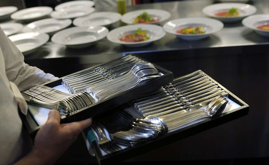 A server walks by the prep line with silverware for table settings in the kitchen during the Top 100 Newcomers fundraising dinner for the San Francisco/Marin Food Bank at The Cavalier in San Francisco, Calif., on Sunday, July 27, 2014. The Chronicle helped organize the dinner as part of the Eat Drink SF festival. Photo: The Chronicle