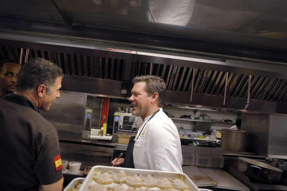 Chefs Michael Chiarello, left, and Tyler Florence chat in the kitchen during the Top 100 Newcomers fundraising dinner for the San Francisco/Marin Food Bank at The Cavalier in San Francisco, Calif., on Sunday, July 27, 2014. The Chronicle helped organize the dinner as part of the Eat Drink SF festival. Photo: The Chronicle