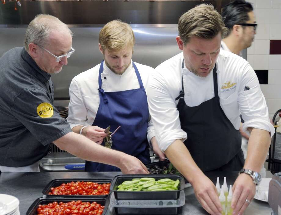 Chef Tyler Florence, right, begins to place items for his course to be prepared on the line in the kitchen during the Top 100 Newcomers fundraising dinner for the San Francisco/Marin Food Bank at The Cavalier in San Francisco, Calif., on Sunday, July 27, 2014. The Chronicle helped organize the dinner as part of the Eat Drink SF festival. Photo: The Chronicle