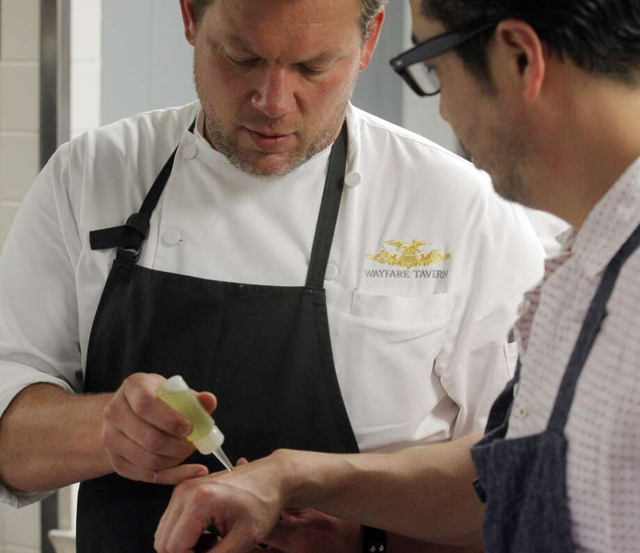 Chef Tyler Florence, left, puts a drop of tomato and grape seed oil on the hand of Chef Shotaro Kamio so he can taste it in the kitchen during the Top 100 Newcomers fundraising dinner for the San Francisco/Marin Food Bank at The Cavalier in San Francisco, Calif., on Sunday, July 27, 2014. The Chronicle helped organize the dinner as part of the Eat Drink SF festival. Photo: The Chronicle