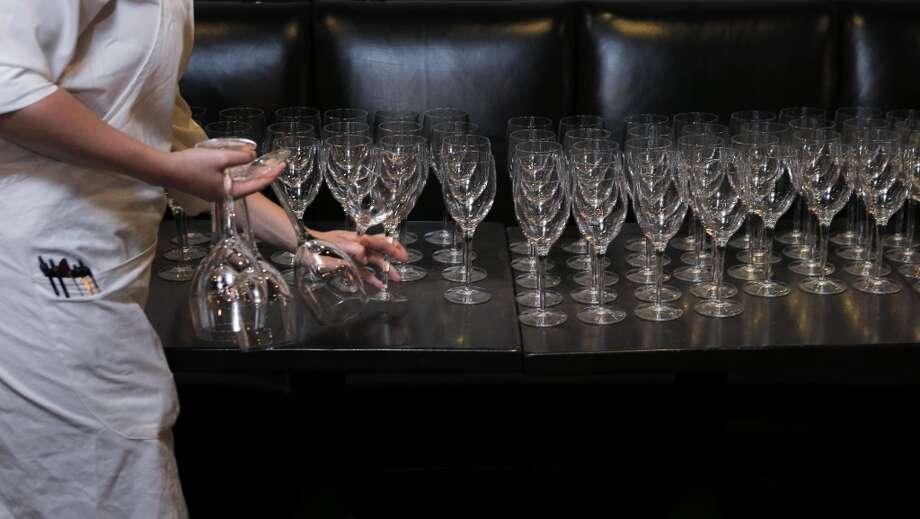A server takes wine glasses out to the dining room during the Top 100 Newcomers fundraising dinner for the San Francisco/Marin Food Bank at The Cavalier in San Francisco, Calif., on Sunday, July 27, 2014. The Chronicle helped organize the dinner as part of the Eat Drink SF festival. Photo: The Chronicle