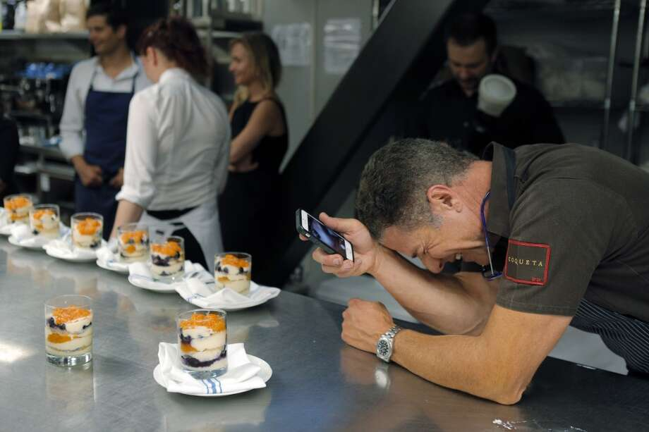 Chef Michael Chiarello laughs as he photographs the desert in the kitchen during the Top 100 Newcomers fundraising dinner for the San Francisco/Marin Food Bank at The Cavalier in San Francisco, Calif., on Sunday, July 27, 2014. The Chronicle helped organize the dinner as part of the Eat Drink SF festival. Photo: Carlos Avila Gonzalez, The Chronicle