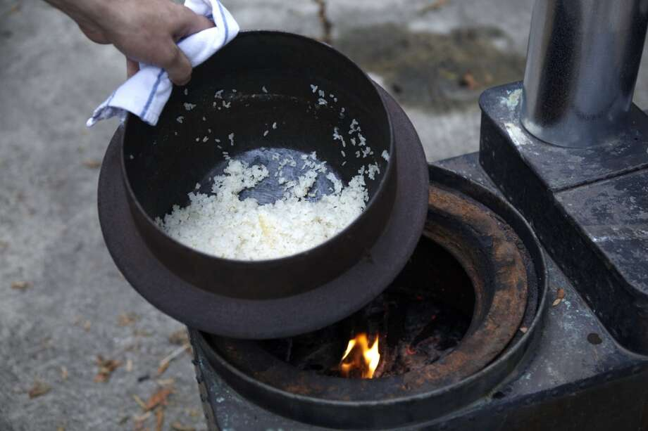 Rice cooks in a pot on the kamado an old  wood-fired stove that Brackett uses for live-fire cooking and parties. Photo: Aya Brackett, Special To The Chronicle