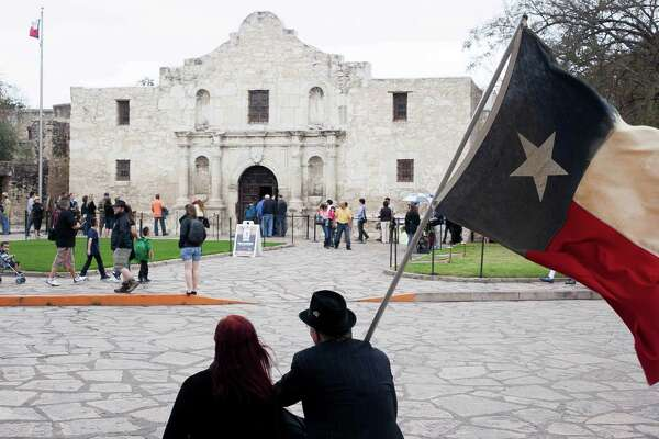 Don and Vikie Schwartz watch people pass through the Alamo while sporting their Texas flag Sunday March 2, 2014 during a short wreath ceremony put on by the San Antonio DRT chapters for Texas Independence Day. Schwartz says though they are not part of the official ceremony, they have made it a tradition to come out to the Alamo every year with their Texas flag.