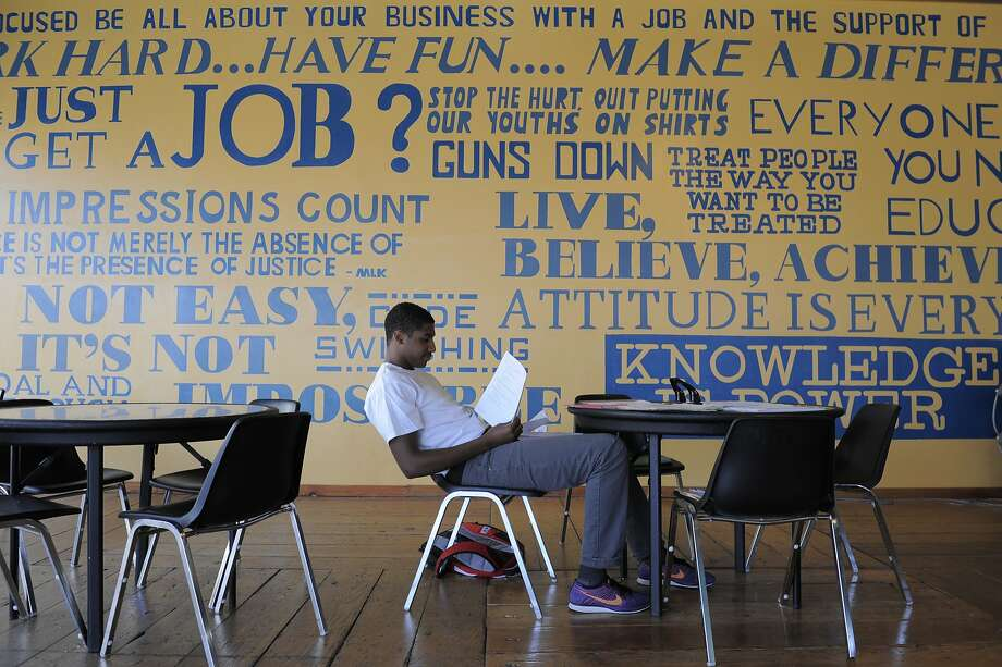 Isaih Hood examines some of his papers in the lobby of the Youth Employment Partnership, which teaches skills to hundreds of Oakland teens while having them do tasks such as office work and trash cleanups. Photo: Craig Hudson, The Chronicle