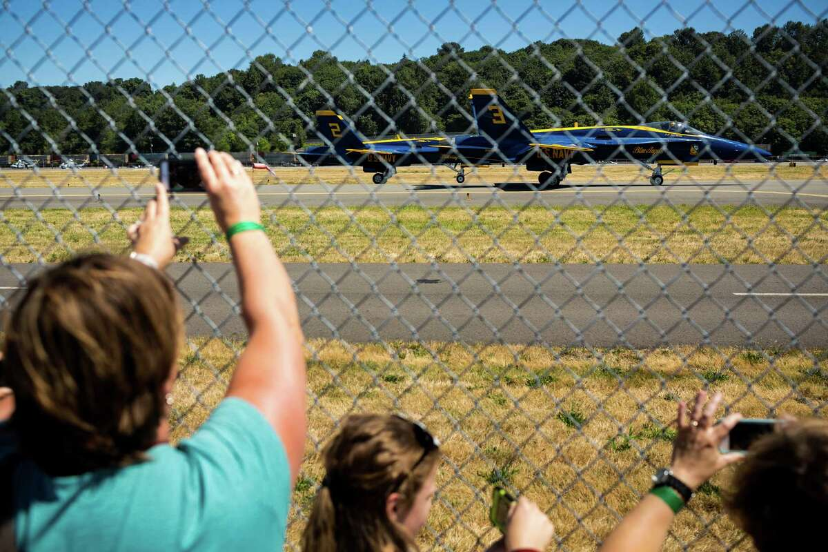 Onlookers photograph the arrival of the U.S. Navy Blue Angels at Boeing Field Monday, July 28, 2014, in Seattle, Wash.
