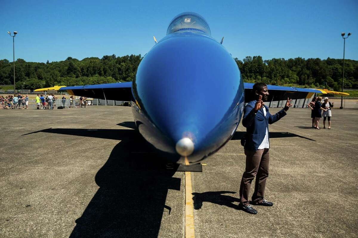 Onlookers pose for pictures by the U.S. Navy Blue Angels at Boeing Field Monday, July 28, 2014, in Seattle, Wash.