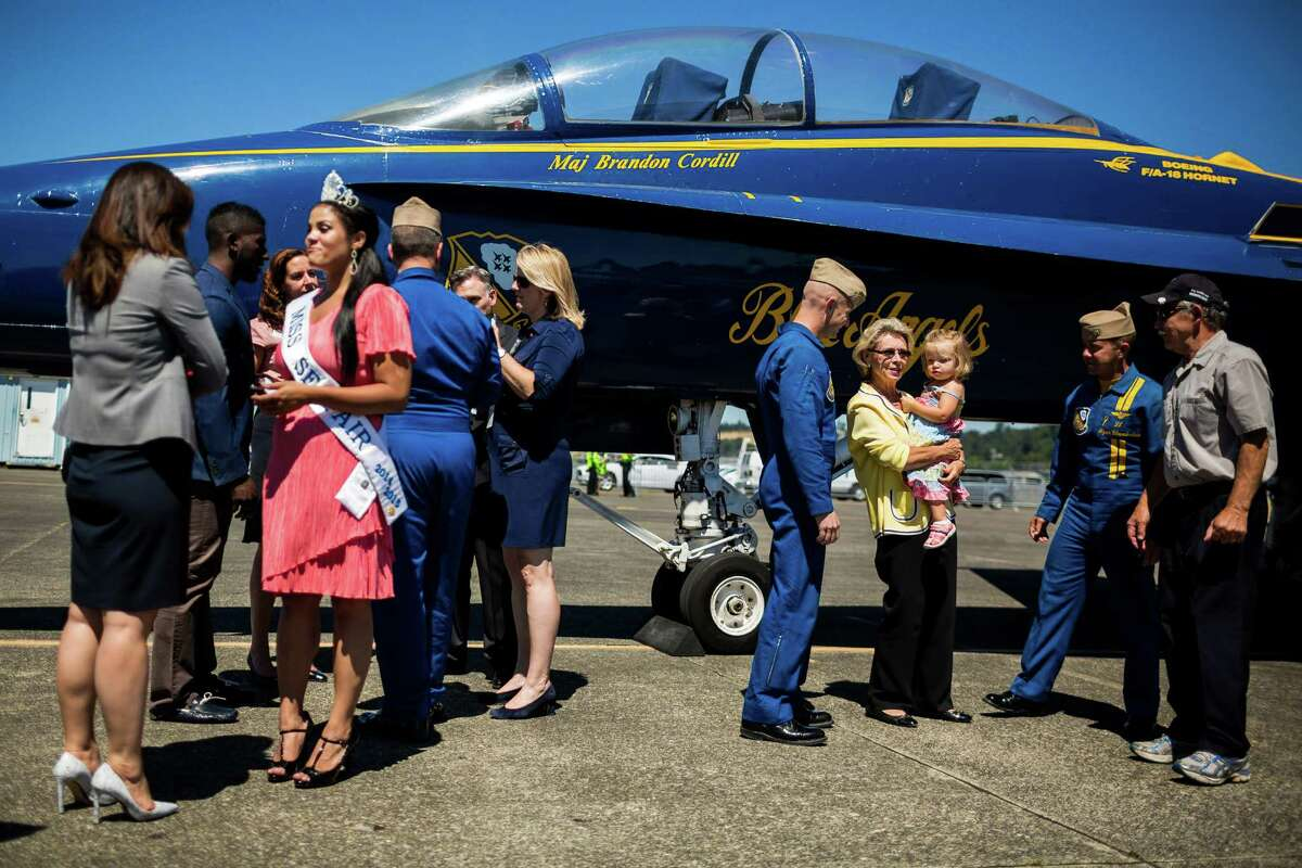 Former Governor of Washington, Christine Gregoire, center right, poses for pictures by the U.S. Navy Blue Angels at Boeing Field Monday, July 28, 2014, in Seattle, Wash.
