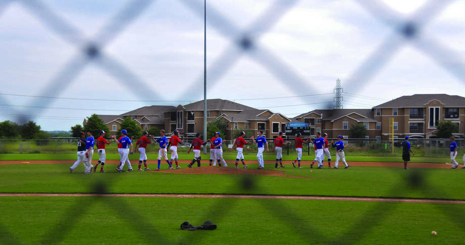 Players from opposing teams in the Bexar County Games baseball tournament July 19 file by each other after one of the competitions, bumping fists in a show of good sportsmanship, win or lose. Photo: Courtesy, San Antonio Sports
