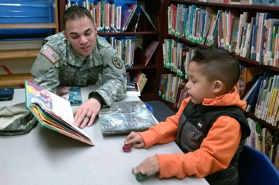 U.S. Army Sgt. Jason McKennon reads to his son, Xaidyn, 5, during a January visit to the Universal City Public Library. Photo: Courtesy Photo