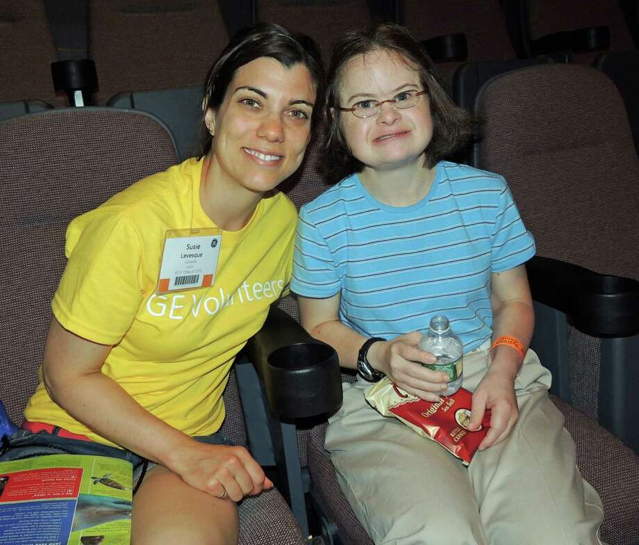 Forty-two adults with developmental disabilities from STAR recently enjoyed a day at The Maritime Aquarium at Norwalk with 42 young professionals from GE. Above, Annie Brautigam, of Darien, enjoys the IMAX movie with GE volunteer Suzie Levesque. Photo: Contributed Photo, Contributed / Darien News Contributed