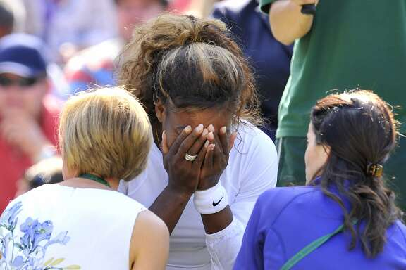 US player Serena Williams (C) covers her face as she sits talking to the doctor on court after being taken ill during her women's doubles second round match playing with US player Venus Williams and against Germany's Kristina Barrois and Switzerland's Stefanie Voegele on day eight of the 2014 Wimbledon Championships at The All England Tennis Club in Wimbledon, southwest London, on July 1, 2014. US superstar Serena Williams was at the centre of a Wimbledon health scare when she wept and appeared to be close to fainting in a doubles match with sister Venus. Serena, the world number one singles player, called the doctor to Court One just after she and Venus had warmed up for their second round match against Kristina Barrois and Stephanie Voegele. She broke down in tears as she consulted with the doctor and physio before the tournament referee and supervisor were called to court in a reflection of her status in the sport. The Williams sisters retired from the match.  AFP PHOTO / GLYN KIRK  - RESTRICTED TO EDITORIAL USEGLYN KIRK/AFP/Getty Images