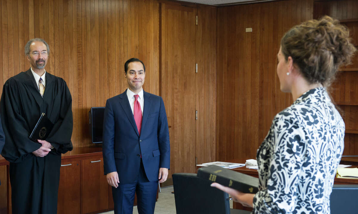 Julián Castro, center, prepares to be sworn in July 28, 2014 as the 16th Secretary for the U.S. Department of Housing and Urban Development. The brief swearing-in ceremony took place at HUD headquarters in Washington, D.C. and was administered by Chief Judge Richard W. Roberts, left, of the United States District Court for the District of Columbia. HUD Chief of Staff Nealin Parker, right, held the Bible during the ceremony.