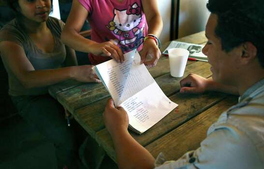 Juan, right, not his real name, teaches English words to two young residents at Casa Rosa de Amor in San Lucas, just outside Antigua, Guatemala. Juan was an orphan himself and was mistreated at an area orphanage.  Wednesday, July 23, 2014. Photo: Bob Owen, San Antonio Express-News / ©2013 San Antonio Express-News