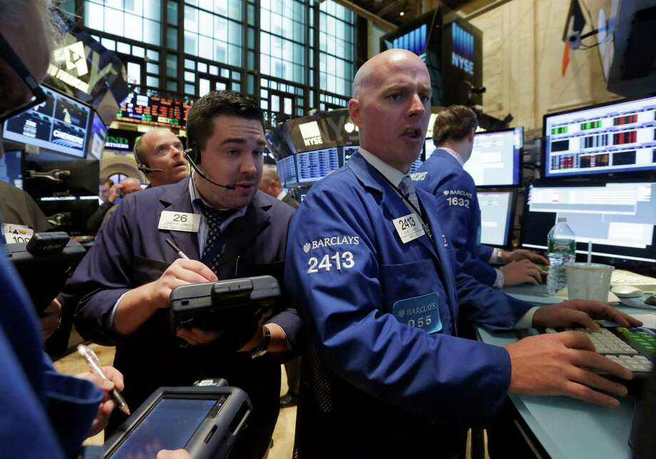 Trader Joseph Lawler, and specialist John O'hara, foreground left and right, work on the floor of the New York Stock Exchange Monday, July 28, 2014. The stock market is opening mixed at the start of a busy week as a batch of merger announcements lift shares in Family Dollar and other companies. (AP Photo/Richard Drew) ORG XMIT: NYRD110 Photo: Richard Drew / AP