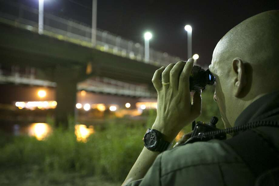A Border Patrol agent keeps watch in Roma, Texas, across from Mexico. There has been a surge in the number of unaccompanied minors crossing the border. Photo: Jay Janner, Associated Press
