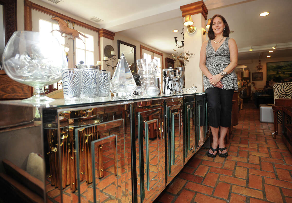 Owner Dottie DeLucawith a mid-century modern Ello mirrored and chromed credenza at Fleur De Lis Antiques and Design at 4 Long Ridge Road in West Redding, Conn., in 2014.