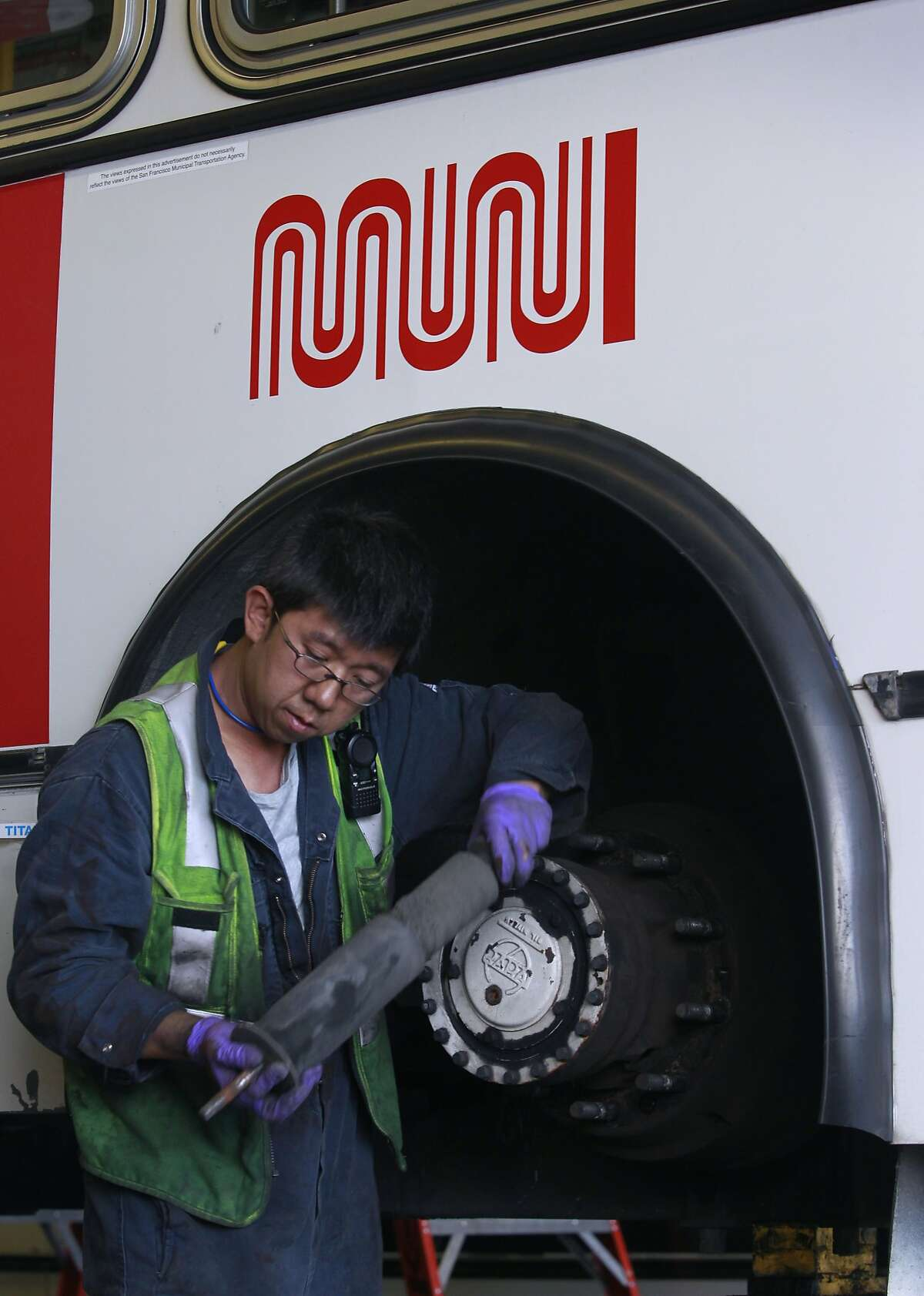 Muni mechanic Tommy To replaces the rear shocks on a trolley bus at the maintenance yard on Presidio Avenue in San Francisco, Calif. on Tuesday, May 20, 2014.