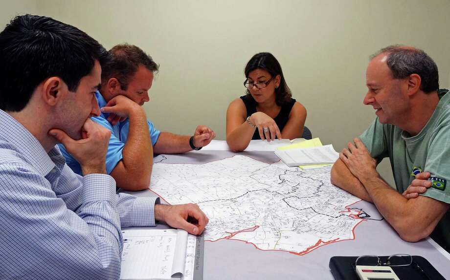 Members of the Representative Town Meeting Redistricting Committee, from left, Phil Pires, Chris Tymniak, Chairman Pam Iacono and Allen Marks, look over a draft redistrict map at a meeting Monday. Photo: Genevieve Reilly / Fairfield Citizen