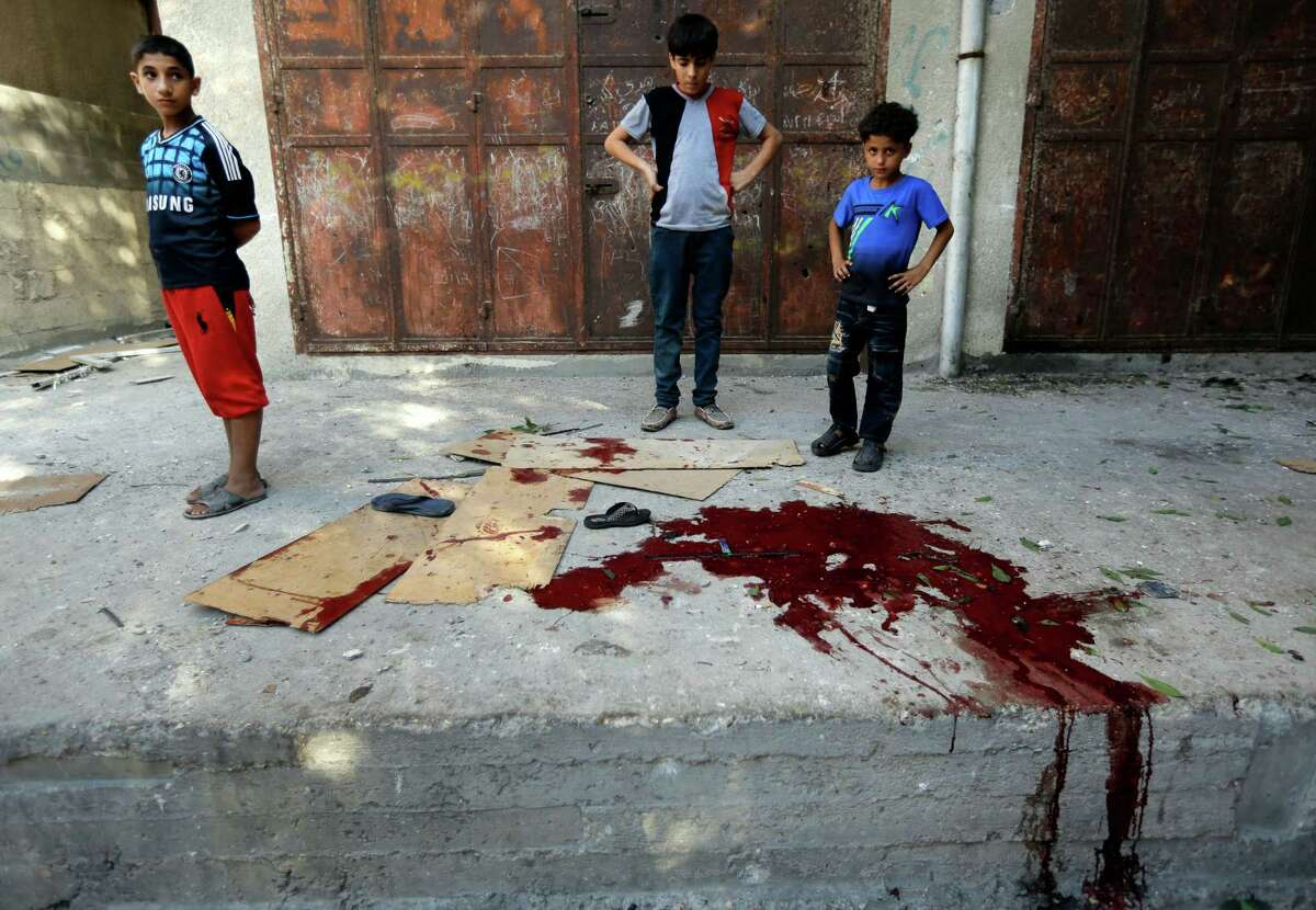 Palestinians look at a pool of blood from victims of an explosion that killed 10 people, 9 of them children, at a park at Shati refugee camp, in the northern Gaza Strip, Monday, July 28, 2014. Israeli and Palestinian authorities traded blame over the attack and fighting in the Gaza war raged on despite a major Muslim holiday. (AP Photo/Lefteris Pitarakis) ORG XMIT: AXLP148