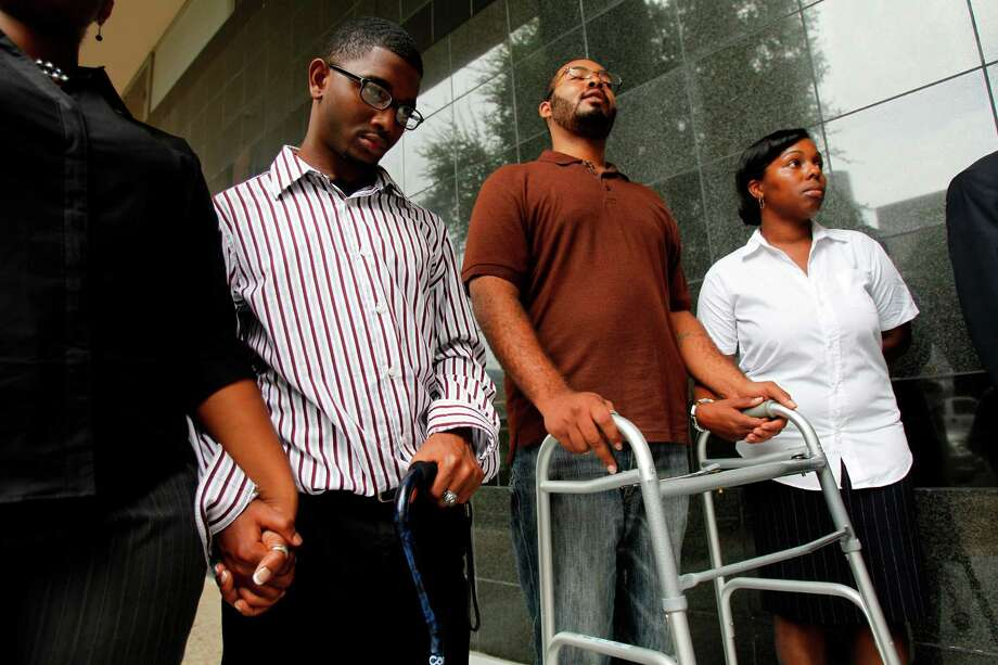 Lisa Bean-Kemp, left, with her brother, Mecole Roques, and Tamika Sewell, right, holding the hand of her son, Dexter, had sought $30 million in their federal lawsuit against the city of Houston. Photo: Melissa Phillip, Staff / Houston Chronicle