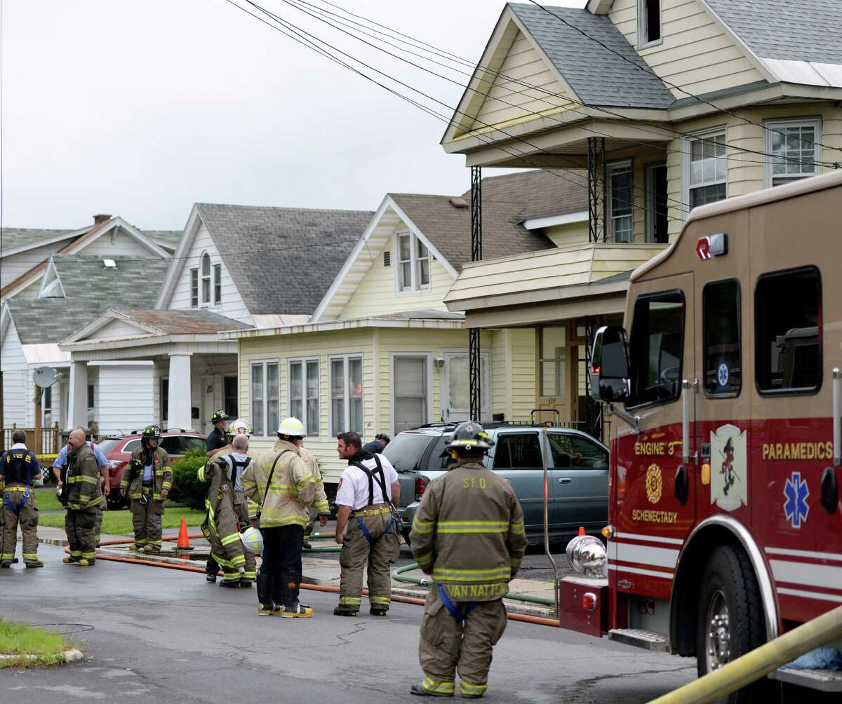 Firefighters and investigators begin the task of determining the cause of a fire at 324 Michigan Avenue Monday morning July 28, 2014 in Schenectady, N.Y. (Skip Dickstein / Times Union)