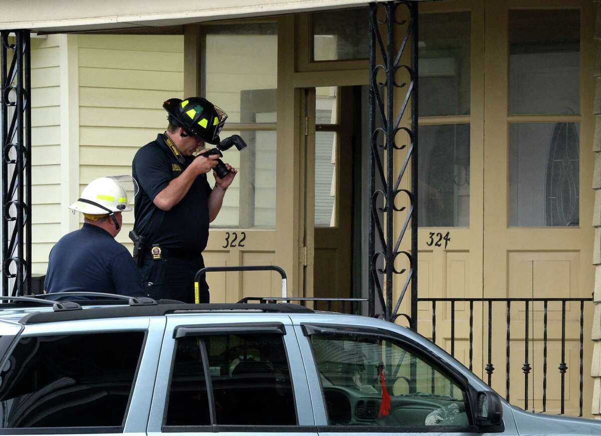 A police forensics investigator makes a photo of evidence at the scene of a fire at 324 Michigan Avenue Monday morning July 28, 2014 in Schenectady, N.Y. (Skip Dickstein / Times Union)