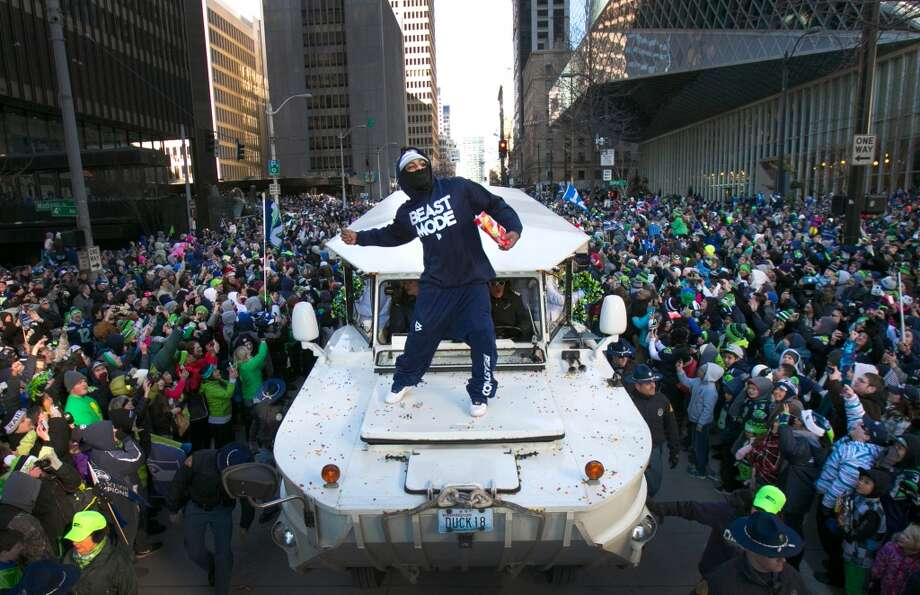 Back in Seattle, Lynch put on a show for the 12th Man during the Seahawks' Super Bowl victory parade. Riding on the hood of a Ride the Ducks vehicle, Lynch threw Skittles to the crowd, took swigs of Fireball whiskey and banged on a ceremonial American-Indian drum he snagged from a fan. Photo: Joshua Trujillo, Seattlepi.com