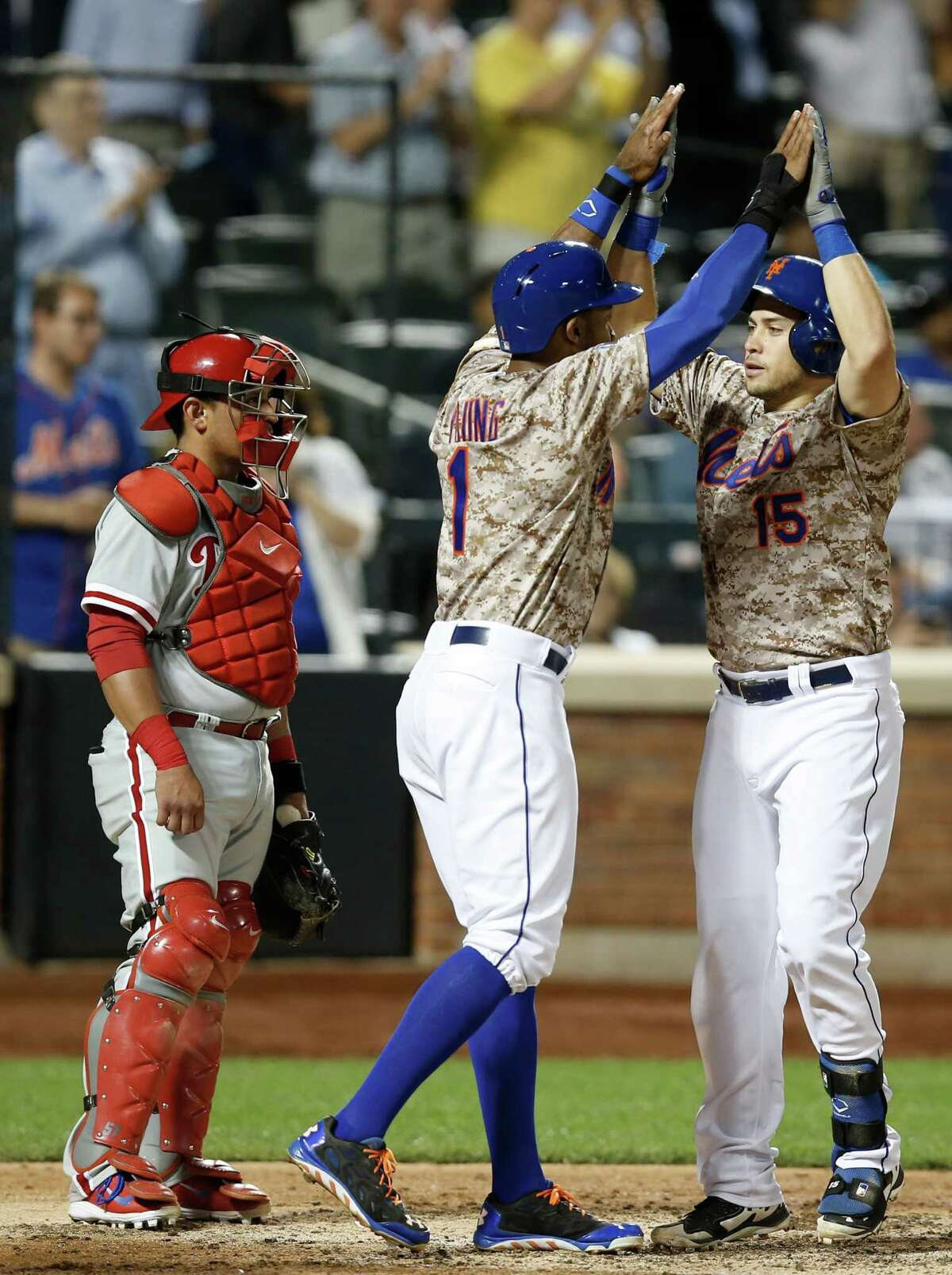 Philadelphia Phillies catcher Carlos Ruiz, far left, watches as New York Mets Travis d'Arnaud , right, (15) celebrates with the Mets Chris Young (1) at the plate after hitting a fifth-inning, three-run, home run off Philadelphia Phillies in a baseball game in New York, Monday, July 28, 2014. (AP Photo/Kathy Willens) ORG XMIT: NYM107