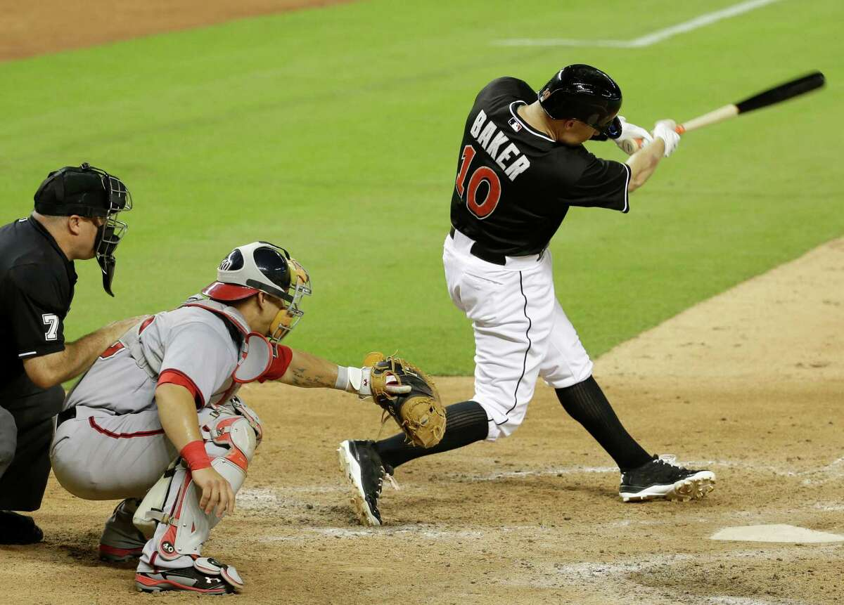 Miami Marlins' Jeff Baker (10) hits a single to drive in Adeiny Hechavarria for the game-winning run in the ninth inning during a baseball game against the Washington Nationals, Monday, July 28, 2014, in Miami. The Marlins defeated the Nationals 7-6. At left is Washington Nationals catcher Wilson Ramos. (AP Photo/Lynne Sladky) ORG XMIT: FLLS118