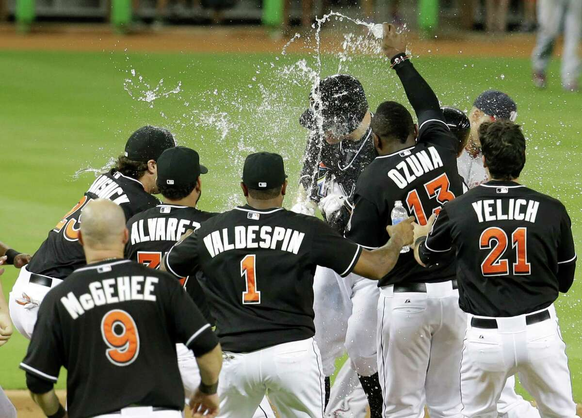 Miami Marlins' Jeff Baker, center, is sprayed with water by Marcell Ozuna (13) after driving in the winning run with a single to score Adeiny Hechavarria in the ninth inning during a baseball game against the Washington Nationals, Monday, July 28, 2014, in Miami. The Marlins defeated the Nationals 7-6. (AP Photo/Lynne Sladky) ORG XMIT: FLLS116