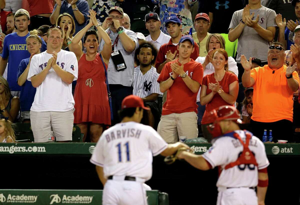 Fans give Texas Rangers starting pitcher Yu Darvish (11) a standing ovation as he fist bumps with catcher Chris Gimenez and leaves the field after the top of the seventh inning of a baseball game against the New York Yankees, Monday, July 28, 2014, in Arlington, Texas. (AP Photo/Tony Gutierrez) ORG XMIT: ARL123