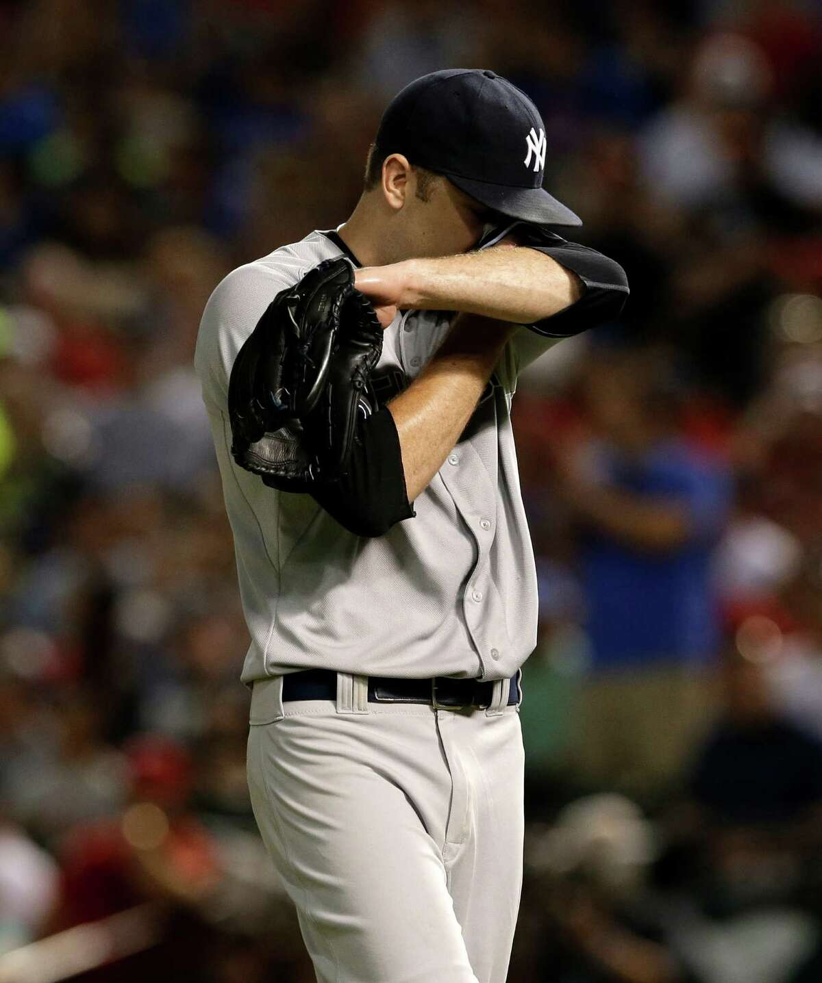 New York Yankees' David Phelps wipes his face as he walks back on the mound after giving up a two-run single to Texas Rangers' J.P. Arencibia in the fifth inning of a baseball game, Monday, July 28, 2014, in Arlington, Texas. (AP Photo/Tony Gutierrez) ORG XMIT: ARL121
