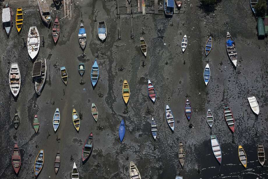 In this Nov. 19, 2013 photo small boats sit on the shore of Guanabara Bay in the suburb of Sao Goncalo, across the bay from Rio de Janeiro, Brazil.  Rio dumps almost 70 percent of its untreated sewage into its surrounding waters, which fouls the bay with human waste and floating debris. (AP Photo/Felipe Dana, File) Photo: Felipe Dana, Associated Press