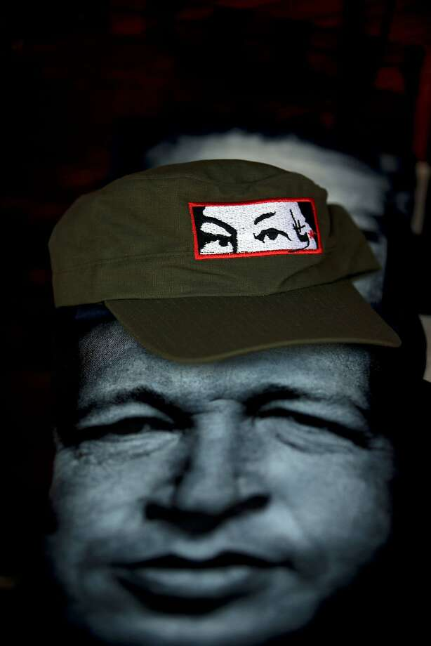 In this Friday, July 25, 2014, photo, a t-shirt with the image of the late Venezuelan President Hugo Chavez is for sale along with a cap, at a street shop in down town Caracas, Venezuela. The Government is preparing to commemorate the birth of the late President Chávez. Had Chavez been alive this would have been his 60th birthday. The official celebrations began early morning with a special commemoration at the Mountain Headquarters where his remains are buried. (AP Photo/Fernando Llano) Photo: Fernando Llano, Associated Press