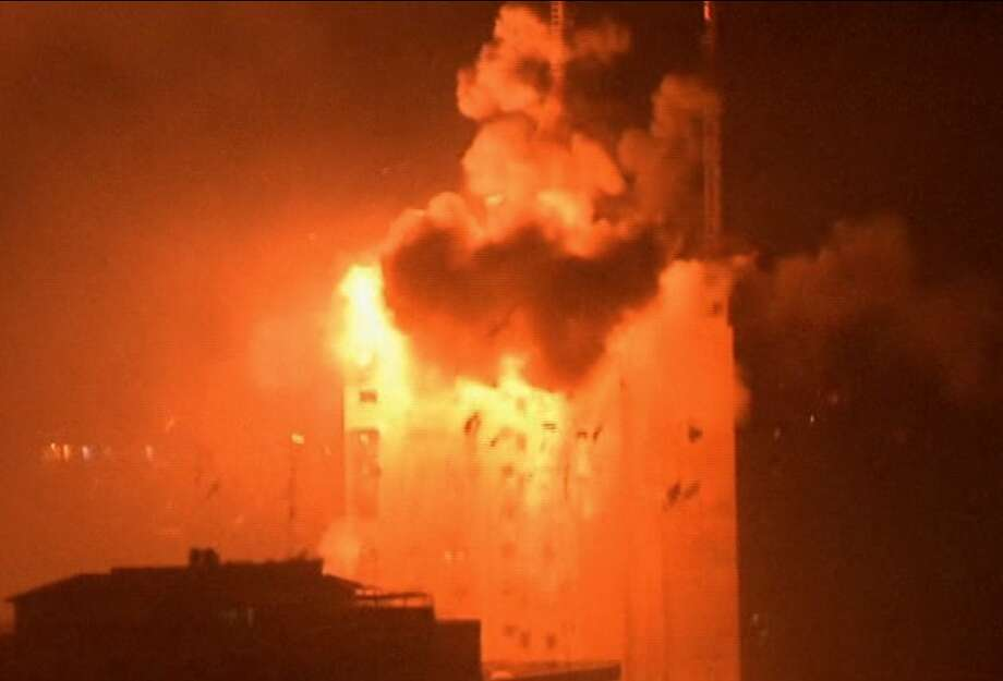 In this image taken from video an explosion hits the media complex that houses the offices of Hamas-run Al Aqsa television and radio in central Gaza City early on Tuesday, July 29, 2014.  The building also houses offices of a number of Arab satellite television news channels. (AP Photo/APTN) Photo: Associated Press