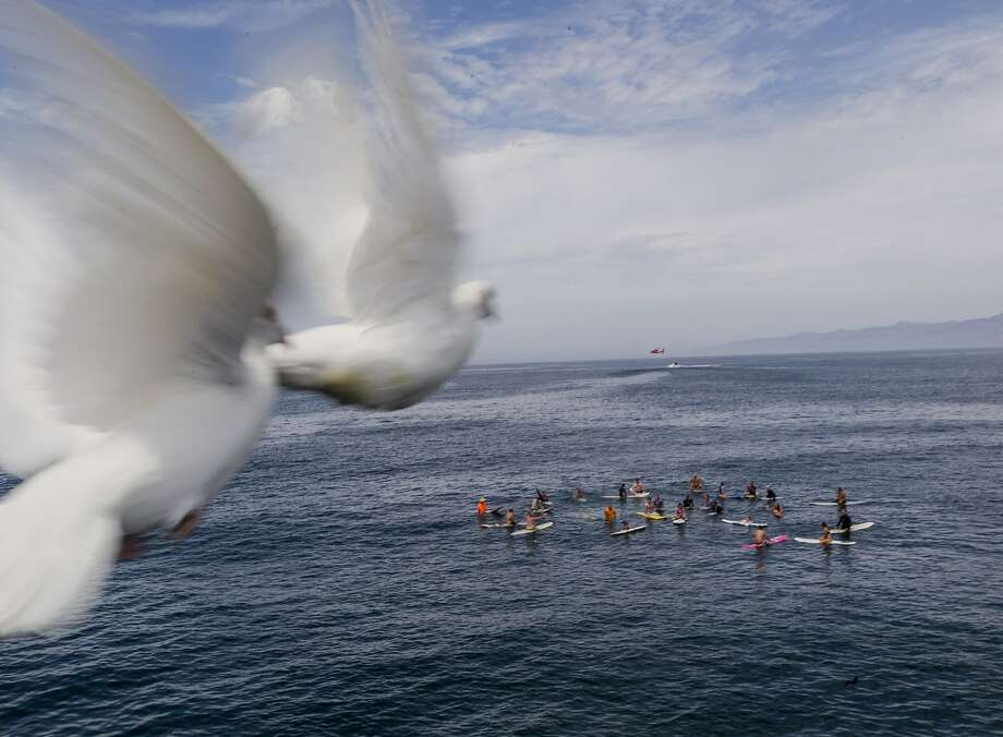 Doves fly away over a memorial paddle-out for Joe Larson, the original owner of Hinano, as the US Coast Guard holds training exercises at Venice Beach in Los Angeles Monday, July 28, 2014. Los Angeles' popular Venice Beach teemed with people enjoying a weekend outing on the boardwalk and sand when lifeguards and other witnesses say lightning from a rare summer thunderstorm hit without warning, injuring or rattling more than a dozen people and leaving a 21-year-old man dead. The witnesses said the strike hit with a tremendous boom about 2:30 p.m. Sunday, rattling buildings and showering a lifeguard headquarters with sparks. (AP Photo/Damian Dovarganes) Photo: Damian Dovarganes, Associated Press