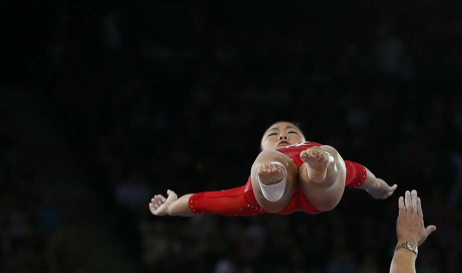 Ashly Lau of Singapore does a warm up vault with the guiding hand of her coach as she prepare to take part in the women's team final and individual qualification for the gymnastics competition at the Commonwealth Games Glasgow 2014, in Glasgow, Scotland, Monday, July, 28, 2014. (AP Photo/Alastair Grant) Photo: Alastair Grant, Associated Press