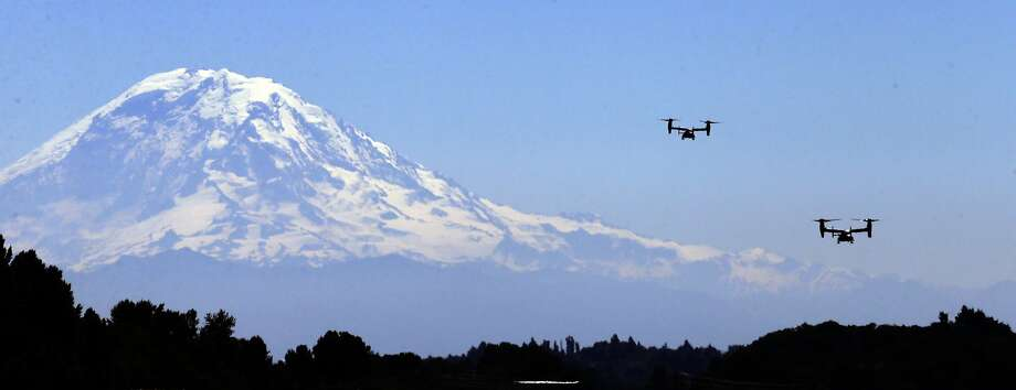 A pair of MV-22B Osprey aircraft fly in view of Mount Rainier during a flight for media members Monday, July 28, 2014, in Seattle. The vertical takeoff and landing tilt-rotor aircraft  is designed to combine the functionality of a conventional helicopter with the performance of a turboprop aircraft. The pair of Osprey are in Seattle in support of Marine Week and will also be part of the annual air show over Lake Washington at Seattle's Seafair festival, Friday through Sunday. (AP Photo/Elaine Thompson) Photo: Elaine Thompson, Associated Press