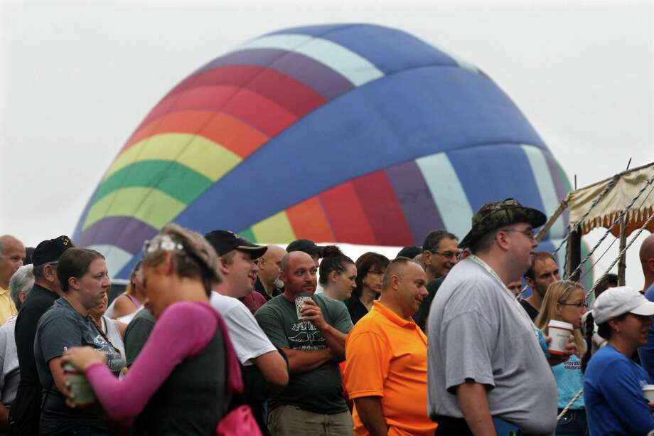 People gather at a demonstration as a hot air balloon inflates nearby at the 32nd annual OuickChek New Jersey Festival of Ballooning Sunday, July 27, 2014, in Readington, N.J.  Photo: Mel Evans, Associated Press / AP