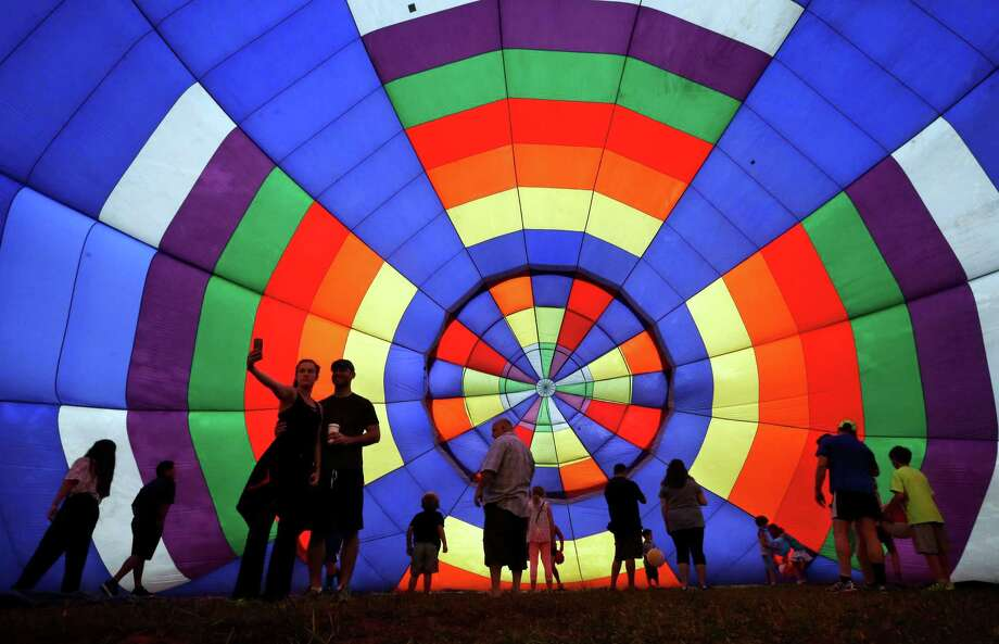 People walk around inside a partially inflated hot air balloon at the 32nd annual OuickChek New Jersey Festival of Ballooning, Sunday, July 27, 2014, in Readington, N.J.  Photo: Mel Evans, Associated Press / AP