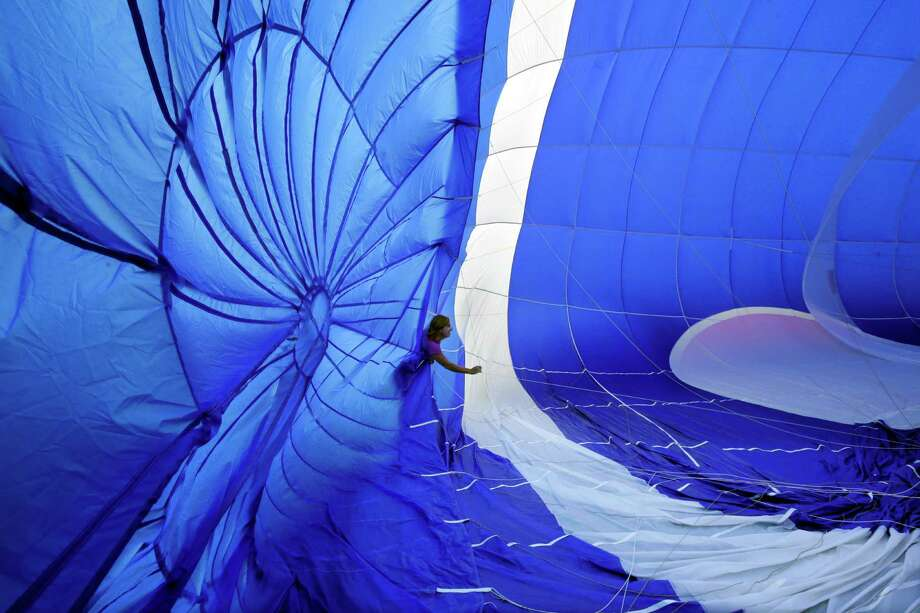 A crew member checks guide wires as a hot air balloon inflates for flight at the 32nd annual OuickChek New Jersey Festival of Ballooning Sunday, July 27, 2014, in Readington, N.J. Photo: Mel Evans, Associated Press / AP