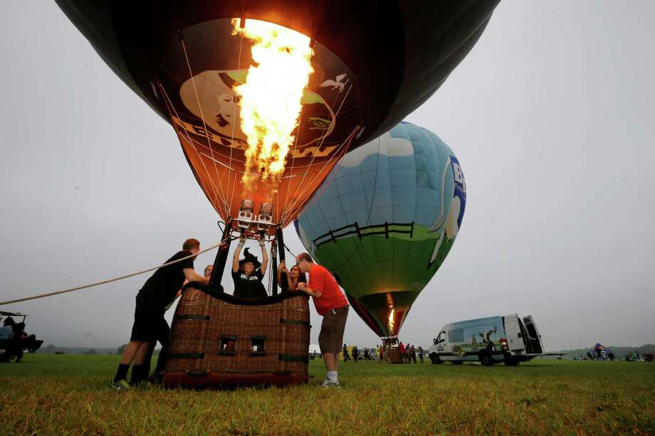 Laura LiAnn Adams, of Elverson, Pa., wears a witch's hat as she inflates her hot air balloon, Wicked, for flight at the 32nd annual OuickChek New Jersey Festival of Ballooning Sunday, July 27, 2014, in Readington, N.J.  Photo: Mel Evans, Associated Press / AP