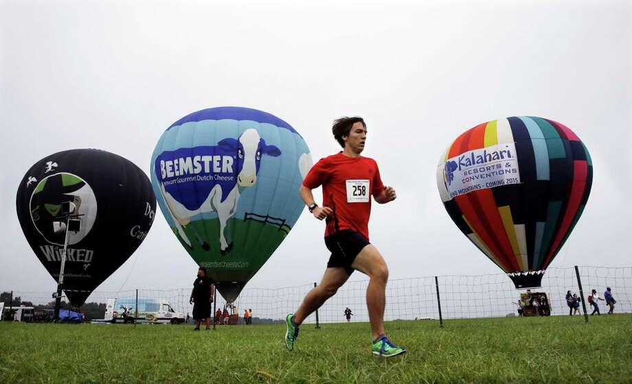 A runner passes hot air balloons  during a 5K race at the 32nd annual OuickChek New Jersey Festival of Ballooning Sunday, July 27, 2014, in Readington, N.J. Photo: Mel Evans, Associated Press / AP