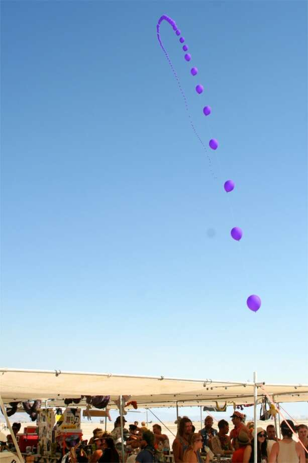 "Balloons! 50? 100? More? There were two strings like this on the playa this year, one purple and one white. They both had a single, bright LED attached to each balloon for a stark and amazing, ""string-of-stars"" effect at night. But daytime was rather wonderful, too."
