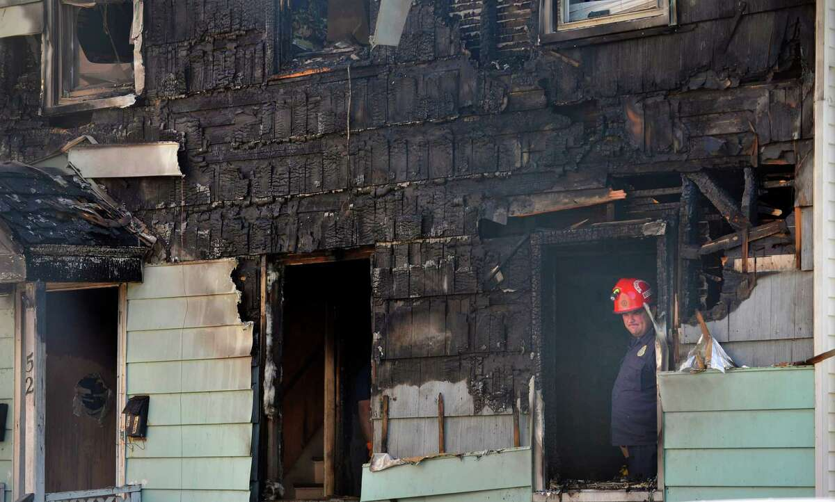 A fire investigator works at the scene of a fatal fire at 52 Walker Street, on Tuesday, July 29, 2014, in Rensselaer, N.Y. (Paul Buckowski / Times Union)