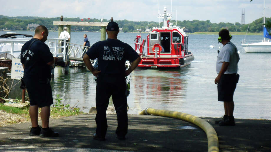 Firefighters monitor the water-supply hose attached to Norwalk's fire boat during a shoreline fire training drill Monday. Photo: Westport Fire Department / Westport News