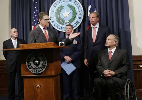 Attorney General Greg Abbott, right, listens as Gov. Rick Perry, at podium, speaks during a news conference in the Governor's press room, Monday, July 21, 2014, in Austin, Texas. Gov. Perry announced he is deploying up to 1,000 National Guard troops over the next month to the Texas-Mexico border to combat criminals that Republican state leaders say are exploiting a surge of children and families entering the U.S. illegally.  (AP Photo/Eric Gay) Photo: Eric Gay, Associated Press